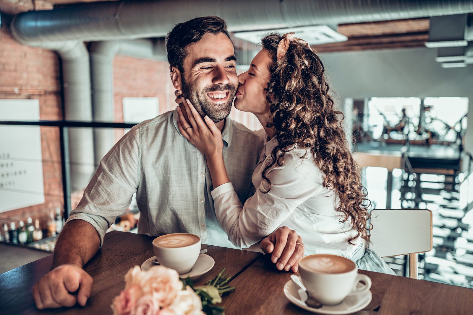 best marriage podcasts - image of man and woman sitting together in a cafe, wife is kissing the husband's cheek as he smiles