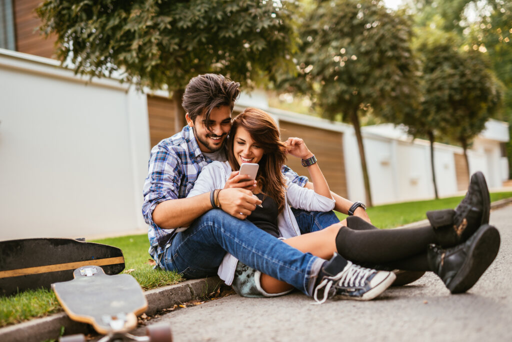 Teenage couple looking at the phone while sitting on a longboard.