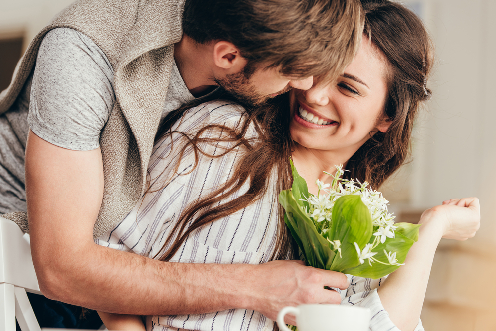 stay at home date night ideas - man and woman with their heads close together laughing and smiling, he is presenting her a bouquet of white flowers