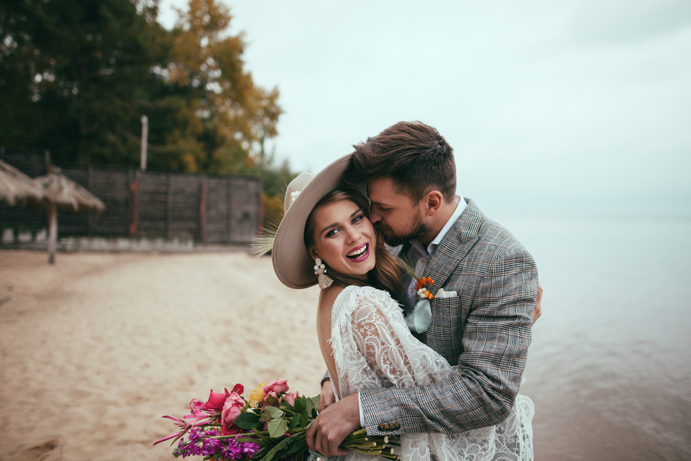 inspirational marriage quotes - couple in wedding clothes kissing on a foggy beach. the man holds pink flowers, the girl wears a hat