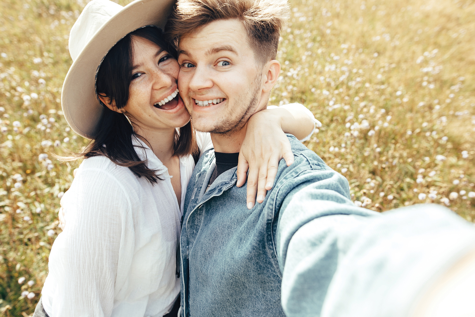 friendship in marriage - young couple taking big smiling selfie together outdoors in a field