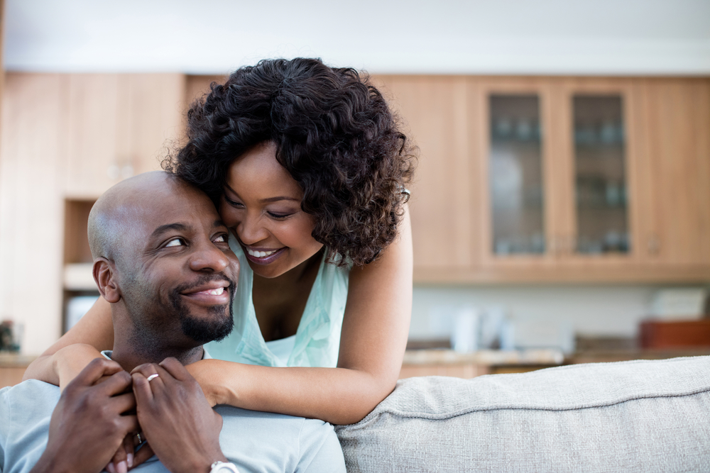 ways to show love and affection - black couple hugging at home, wife stands behind husband who is seated on couch. they smile at each other