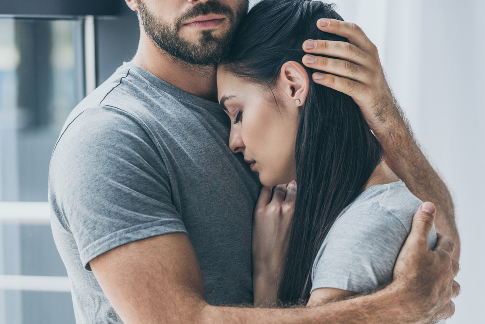 marriage mistakes header - image of husband hugging wife to his chest, cradling her head against him. she has dark black hair