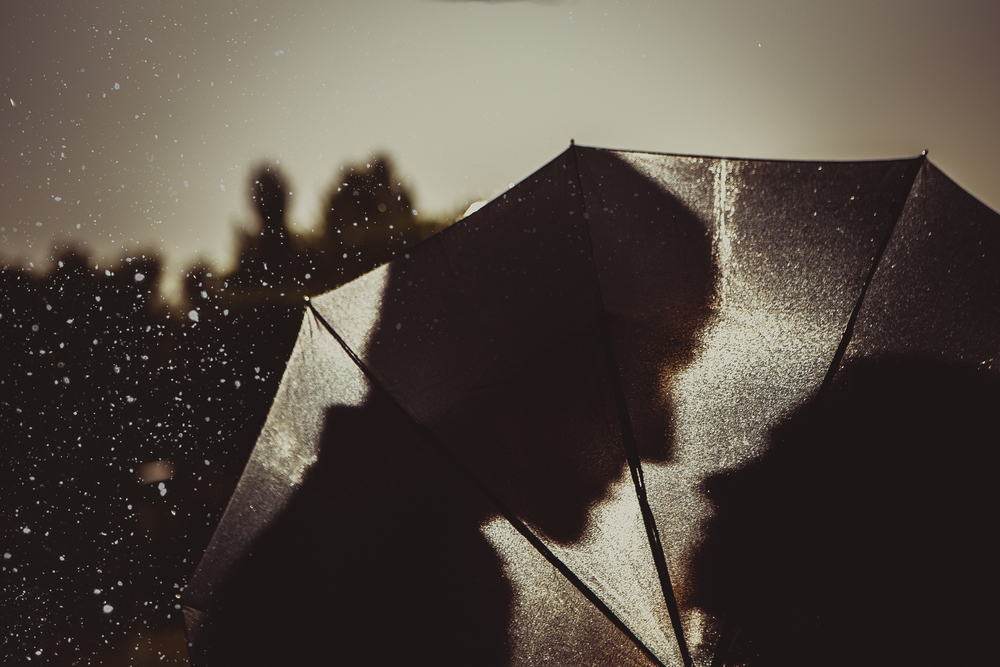 most romantic movies of all time - sepia image Love in the rain / Silhouette of kissing couple under umbrella