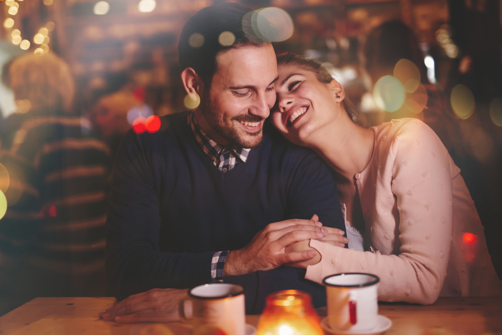 what a husband needs from his wife - couple cuddling and laughing at restaurant in the evening