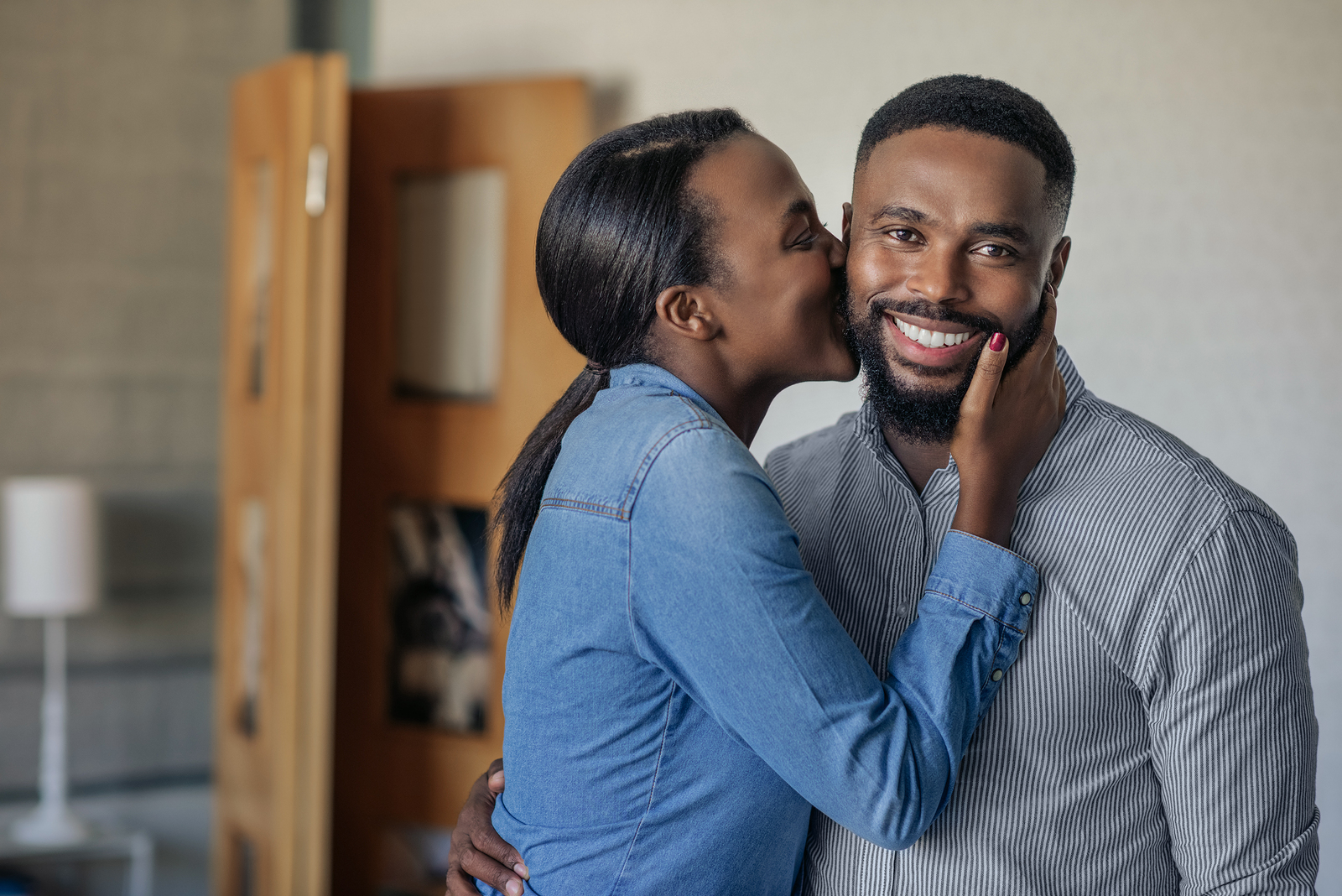 how to be a better wife - Affectionate African American wife kissing her husband on the cheek