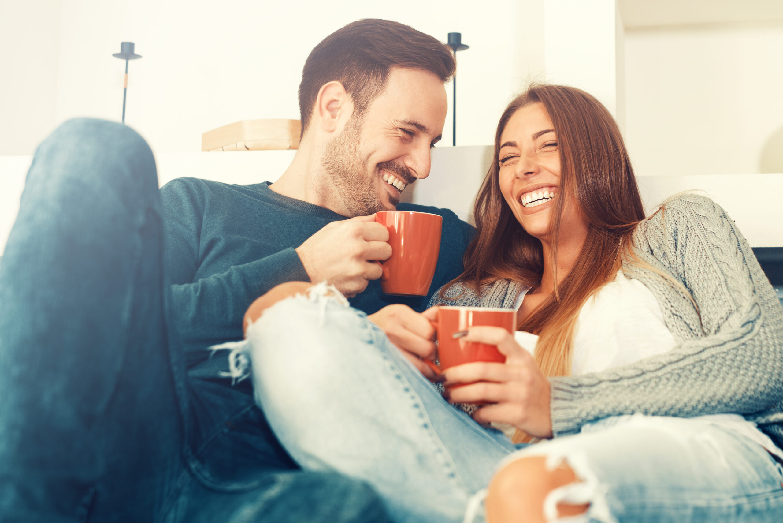 best marriage books for couples - cute white couple sitting on the couch with red mugs and laughing together