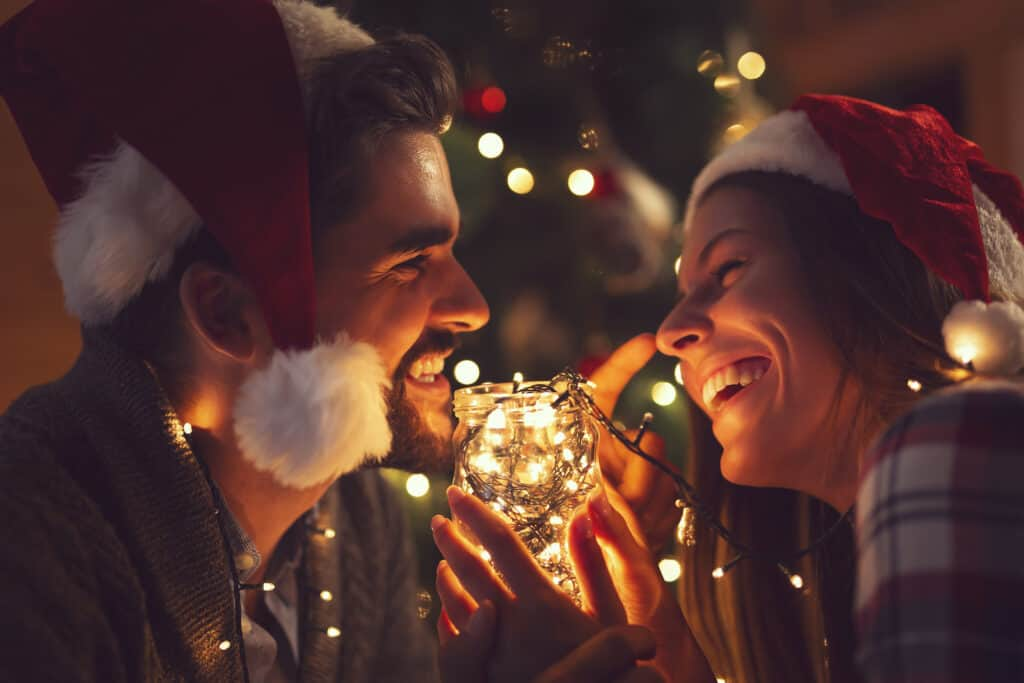 christmas gifts for newlyweds - couple in santa hats smiling and laughing next to illuminated christmas tree