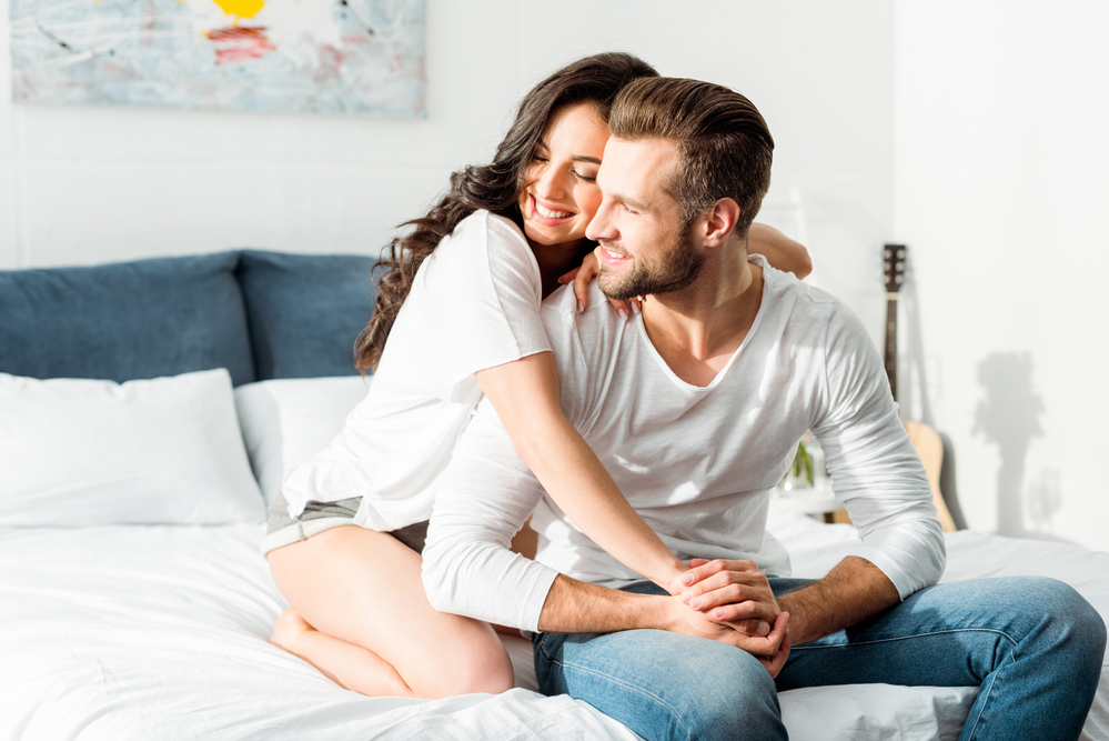couples communication exercises - image of couple hugging on bed, wearing light colored clothes and smiling